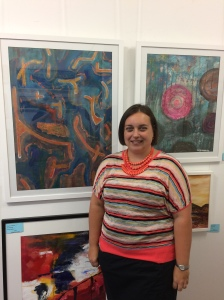 "Pictured: Margo Humphries with two of her paintings for sale at Ocean Blue Gallery's current exhibition: On the left: ""Embarrassed Watermelon"" $500 framed 72 cm w x 96 cm h. Acrylic on paper. On the right: ""Happy Trails"" $400 framed 63 cm w x 77 cm h. Acrylic & ink on board."